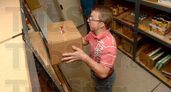 Tribune-Star/Joseph C. Garza<br /> Filling those empty shelves: Volunteer Jarod Anderson, 12, places a box of food on top of a shelf at the Salvation Army Wednesday.