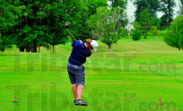 Tribune-Star/Joseph C. Garza<br /> Driving in the rain: Terre Haute North's Sam Pollock tees off on the fourth hole of the Phil Harris Golf Course during sectional play Monday in Linton.