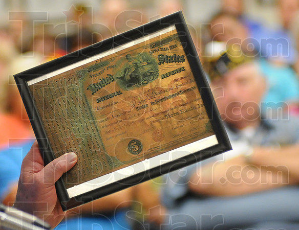 Tax stamp: West Terre Haute resident Kenny Lamb holds tax stamp from 1929 as he makes his case for smoking during Tuesday's meeting.