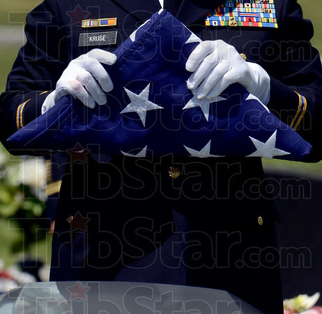 Tribune-Star/Joseph C. Garza<br /> The shape of history: U.S. Army Col. Bernie Kruse holds the flag that covered the casket of Spc. Arronn Fields after it was folded by an honor guard Tuesday at Clearview Cemetery near Brazil. The shape of the folded flag is like that of a bicorne hat which was worn by the troops under Gen. George Washington.