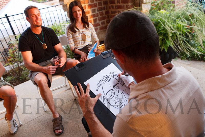 Chris Marks and Seanna Forey have their caricature done by Rich Barry.  Janet's Camp, benefiting the YMCA of Metropolitan Denver, at the home of Steve and Nikki Lockton in Englewood, Colorado, on Saturday, June 23, 2012.<br /> Photo Steve Peterson