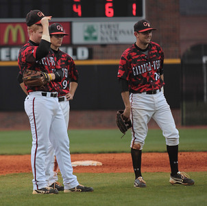 Infielders, Brad Collins(left), Henry Rundio, and Scott Johnson(right) watch during the pitching change
