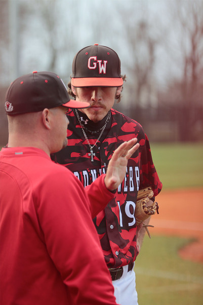 Assistant Coach Ray Greene, talks with pitcher, Brock Wilson, between innings