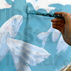 Tribune-Star/Joseph C. Garza<br /> For the flying fish: Indiana State junior art major Jane Thornberry paints the blue water around a fish on the new mural at the Terre Haute Children's Museum Thursday.