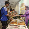 Tribune-Star/Jim Avelis<br /> Cross cultural connections: Neel Iyer, a Rose-Hulman graduate student from India, accepts a plate of Persian food, eggplant and chicken, from Mahvash Hariri. Hariri, who teaches Immunology at IU Med School, was at the Food for Thought event with her husband Hossein, RHIT professor of Chemical Engineering.