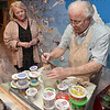 Tribune-Star/Joseph C. Garza<br /> Just the right mix: Indiana State professor emeritus David Erickson mixes paint for junior art major Connie Sisson as they work on the new mural at the Terre Haute Children's Museum Thursday.