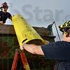 Tribune-Star/Joseph C. Garza<br /> Teamwork: Honey Creek Fire Department probationary firefighter Harold Osborn hands a grain rescue panel to Battalion Chief Chris Lynch for a demonstration Thursday at Station 91.