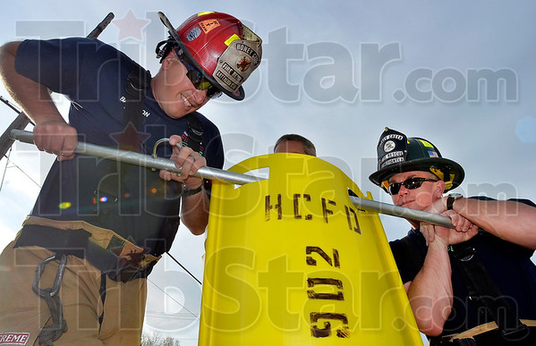 Tribune-Star/Joseph C. Garza<br /> Safely in place: Honey Creek Fire Department Battalion Chief Chris Lynch and firefighter Barry Lilley secure one of the grain rescue panels into place as the demonstrate how the system is used to rescue fellow firefighter Terry Clinkenbeard during a demonstration Wednesday at the Station 91.
