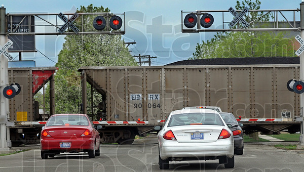 Slow going: A slow moving train travels northbound on the CSX tracks where they cross Walnut Street Sunday afternoon in the downtown area.