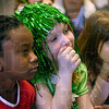 Tribune-Star/Joseph C. Garza<br /> Can he do it?: Sugar Grove Elementary Kindergartners Shadi Benford, Raven Key and Madison Selvia watch as a leprechaun, a.k.a. Pat Sheehan, uses a wee bit of Irish magic to transform potatoes into donuts during his visit to the school Friday.