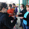 "Tribune-Star/Jim Avelis<br /> Can't wait: Travella Myers, right, doles out some of the 40 tickets she bought to some of the group of girls arriving to see ""The Hunger Games"" Friday evening."