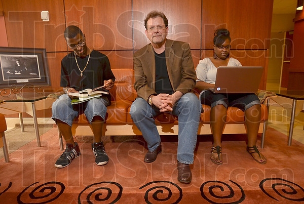 """Tribune-Star/Joseph C. Garza<br /> For the student body: Architect Steve Arnold of MMS poses for a photo between Indiana State students Kevin Flowers, 21, of Michigan City and Vanesha Washington-Mack, 28, of Gary Thursday in a lounge area he designed and which he describes as """"Collegiate Gothic"""" in Stalker Hall on the Indiana State campus."""