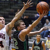 Tribune-Star/Jim Avelis<br /> Out of reach: Jordan Houser slips under the block of Edgewood's Cameron Walls for a layup.