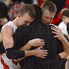Tribune-Star/Jim Avelis<br /> It's over: North Knox coach Aaron Hall comforts two of his seniors, John Michael Rodrick and Jack McKinnon, in the closing seconds of their sectional loss to Eastern Greene.
