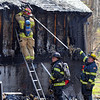 Tribune-Star/Jim Avelis<br /> All out: Firefighters look over the outside on a home on Crews Road west of West Terre Haute Wednesday afternoon. A brush fire got out of hand and damaged the dwelling.