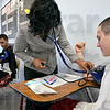 Tribune-Star/Joseph C. Garza<br /> Classroom pressure: Indiana State University student Destiny McCormick takes the blood pressure of McLean High School student Manuel Rivera during a health fair at the school Wednesday.