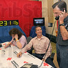 Tribune-Star/Jim Avelis<br /> Personal touch: WTWO/WAWV weatherman Jesse Walker chats with a donor during Tuesday's telethon. Volunteer Curt Pendergast was manning the phones when the call came in asking to talk with Walker. Behind Pendergast is fellow volunteer Joann Brown