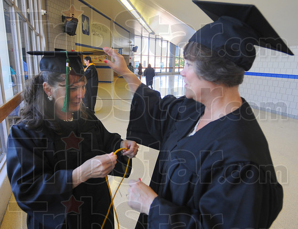Tribune-Star/Jim Avelis<br /> Encore: Brenda Spiering gets a hand with her cap and gown from classmate Barbara Wilson. The two Ivy Tech Community College Wabash Valley grads received  and associates degree Thursday evening. They are both graduates from ITCCWV from the late 1970's in the Allied Health field.