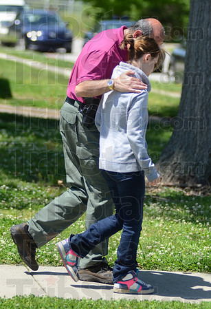 Tribune-Star/Jim Avelis<br /> Safe: Vigo County Sheriff's deputy Frank Shahadey talks with Alyssa Sedletzeck as he leads her away from the house where she had been found. The home owner alerted the sheriff's department.