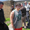Tribune-Star/Jim Avelis<br /> In custody: Brandon Bennett, center, walks to a sheriff deputies' vehicle from his home in the 2900 block of Fenwood Avenue in Terre Haute. Bennett has been charged with two counts of child molesting.