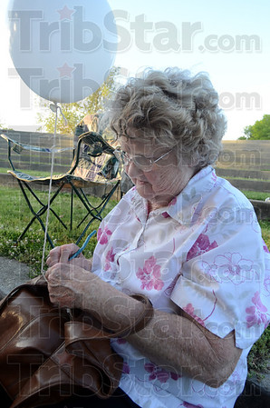 Tribune-Star/Jim Avelis<br /> Hear my prayer O Lord: Doris King writes a prayer on an index card before tying it onto a balloon. The balloon launch ended he National Day of Prayer observance at Fairbanks Park Thursday evening.