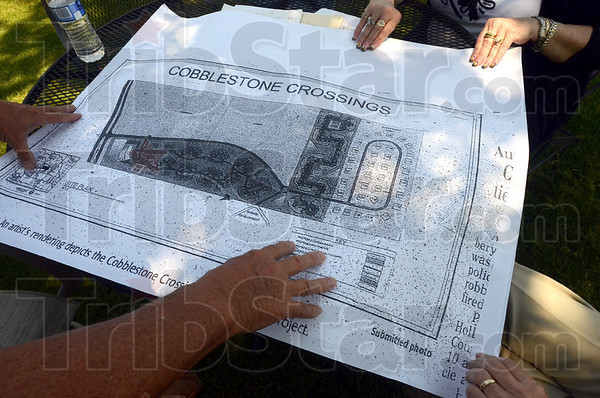 All hands: Several area residents look at a Cobblestone Crossings rendering during a meeting Friday afternoon.