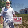 Posted: Rick Wheeler shows the sign he's using to mark his property near the Cobblestone complex.