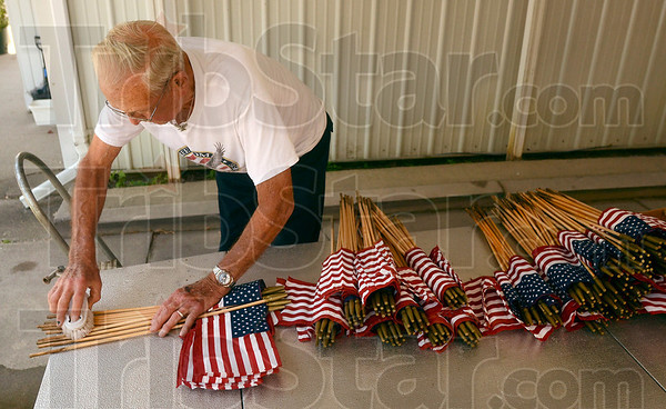 Tribune-Star/Joseph C. Garza<br /> Giving them a good scrubbing: Sonner Faught scrubs the sticks of grave marker flags May 18 at his home in Sullivan. Sonner worked in tandem with his wife Joann by cleaning the flags first and then Joann would iron the flag itself.