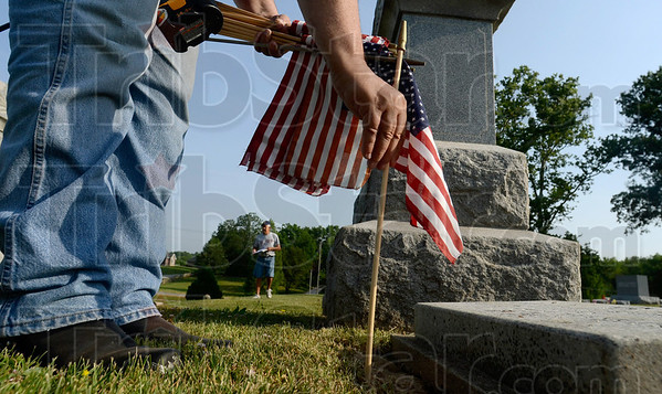 Tribune-Star/Joseph C. Garza<br /> For one who served: Sullivan American Legion Post 139 member John Parris places a flag into the ground near a veteran's grave marker Saturday at Center Ridge Cemetery. The flags that Parris and other volunteers were marking veterans' graves with were cleaned and pressed by Sonner and Joann Faught the week before.