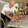 Tribune-Star/Joseph C. Garza<br /> Spring cleaning: Sonner Faught uses a hose to wash off the sticks of grave marker flags May 18 at his home in Sullivan. Faught recycles the flags by washing the stick off while his wife, Joann, makes them even more presentable by ironing them.
