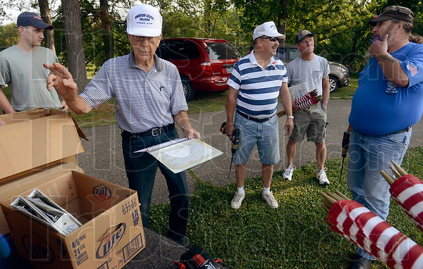 Tribune-Star/Joseph C. Garza<br /> Take that section: After handing a volunteer the proper amount of flags, Sonner Faught points in the direction of the section of Center Ridge Cemetery where the flags need to be placed Saturday morning in Sullivan.