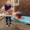 Tribune-Star/Joseph C. Garza<br /> Pressed Stars and Stripes: After her husband, Sonner Faught, washed off the stick of over 600 grave marker flags, Joann Faught, would carefully press each flag with an iron May 18 at the couple's home in Sullivan.