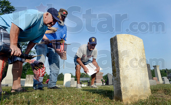 Tribune-Star/Joseph C. Garza<br /> Could this be the one?: American Legion Post 139 members Ron Moreland, John Parris and Jerry Smith scrutinize the etched name in an old grave marker in Center Ridge Cemetery Saturday in Sullivan. The trio were placing small flags on the graves of veterans but were sometimes hindered by century-old markers that were worn by time and the elements and were difficult to read.