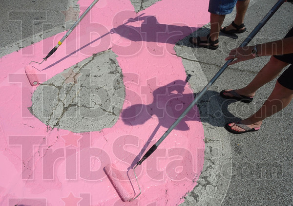 A shadow: Volunteers paint the pink ribbon in the intersection of 6th and Wabash Sunday afternoon.