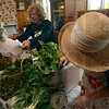 Tribune-Star/Joseph C. Garza<br /> Weighing green: Cathy Hayden, right, weighs some of the produce out of her and her husband Ron's garden at the Farmers Market Saturday at Clabber Girl.