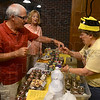 Tribune-Star/Joseph C. Garza<br /> Bee my guest: Beverly Riley, right, offers a sample of her honey to David Bell as Marti Bell looks on Saturday at the Farmers Market in Clabber Girl.