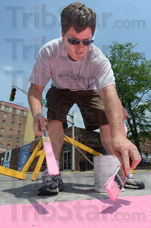 Painter: Volunteer Steve Storey paints the pink ribbon in the intersection of 6th and Wabash Sunday afternoon.