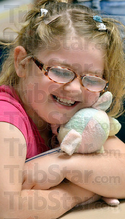 """Tribune-Star/Joseph C. Garza<br /> Her """"bear""""y own Reading Buddy: Davis Park Elementary School first-grader Cassandra Burgess couldn't help but give a big hug to her Reading Buddy after receiving it from a United Way of the Wabash Valley volunteer Friday at the school."""