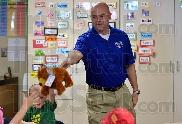 Tribune-Star/Joseph C. Garza<br /> A buddy for reading success: Troy Fears, executive director of the United Way of the Wabash Valley, tosses a stuffed bear to a first-grader at Davis Park Friday morning. Fears and other United Way members and volunteers delivered Reading Buddies to the first graders as part of the United Way's Success By 6 program.