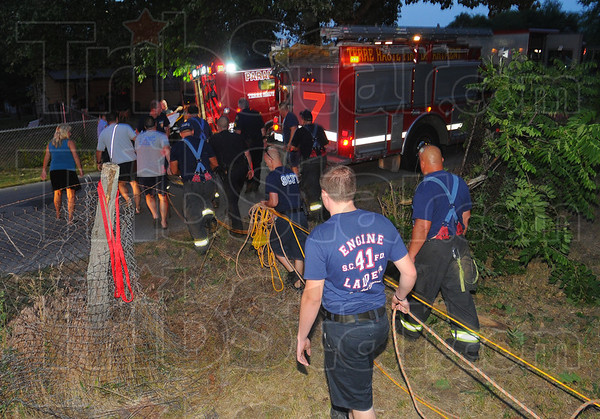 Tribune-Star/Jim Avelis<br /> Rescuers: Emergency personnel wheel a drowning victim to a waiting ambulance Friday night. The unconscious white male had to be lifted/pulled up the north bank of Crystal Lake to Boston Avenue.
