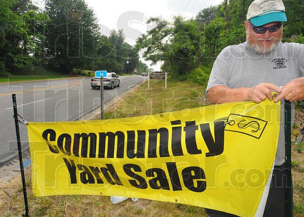 Tribune-Star/Jim Avelis<br /> Big sale: Wayne Langman hangs a sign on the east edge of Seelyville Friday afternoon. The Vigo county town will be will be taking part in the National Road yard sale. The event runs from May 30-June 3.