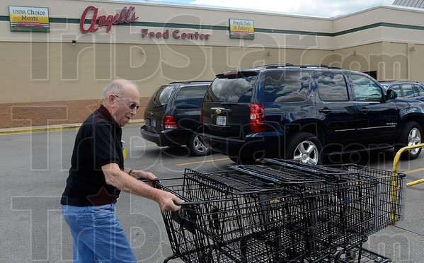 Tribune-Star/Joseph C. Garza<br /> New start for these carts: Angell's Food Center employee Harold Rice backs up a line of shopping carts to take inside for customers Wednesday at the Sullivan store. Angell's Food Centers in Sullivan and Linton will soon be taken over by Baesler's.