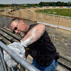 Tribune-Star/Joseph C. Garza<br /> This for T.H.A.T.: Bob Cook of Duke Energy adds a coat of silver paint to the bleachers at the Terre Haute Action Track Wednesday at the Wabash Valley Fairgrounds during the company's Global Service Event.