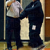 Tribune-Star/Joseph C. Garza<br /> Look what's coming: Sarah Scott Middle School media specialist Tony Smodilla, right, tries to get the attention of a Terre Haute Police Department K-9 officer as he wears the unit's new bite suit with the guidance of Sgt. Terry John Monday at the school.