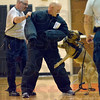 Tribune-Star/Joseph C. Garza<br /> Feel the adrenaline but not the bite: Sarah Scott Middle School librarian/media specialist Tony Smodilla tries to shake a Terre Haute Police Department K-9 officer loose Monday during a demonstration of the unit's new bite suit at the school. Helping Smodilla is the unit's Sgt. Terry John.