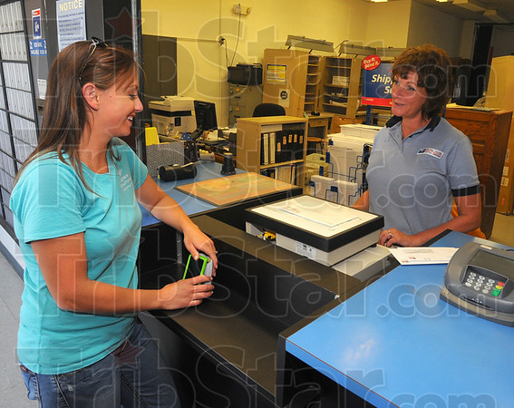 Tribune-Star/Jim Avelis<br /> Easy access: Autumn Dayhoff chats with Clay City Post Master Deanna Meyer after posting a letter Tuesday afternoon.