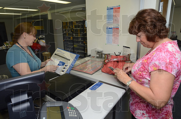 Tribune-Star/Jim Avelis<br /> Personal service: Acting Post Master Amy Tickle waits on Riley resident Sandy Shugars Tuesday afternoon. The Riley Post Office is one of the rural centers that may have its hours cut under new proposals.