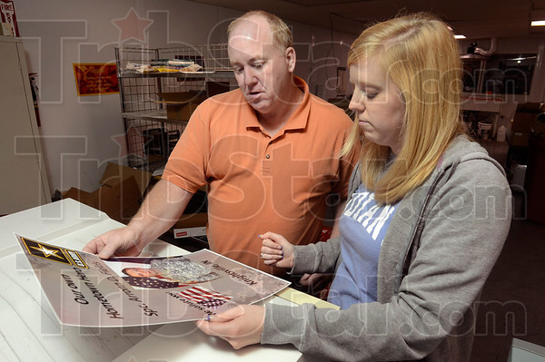 Tribune-Star/Joseph C. Garza<br /> Initial design: Chris Nichols, purchasing manager, and Ellen Coole, graphic designer, of National Printing Converters, Inc., look over an initial printing of the poster for the late U.S. Army Spc. Arronn Fields at the printing facility in Brazil Tuesday.
