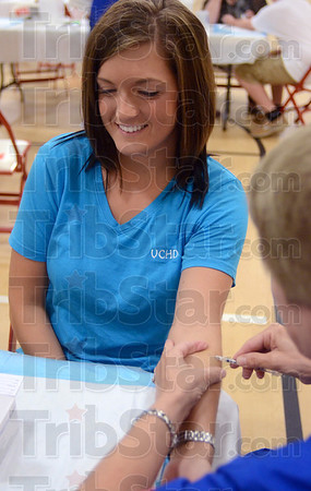 Tribune-Star/Joseph C. Garza<br /> Easy procedure: Sydney Elliott, health educator of the Vigo County Health Department, watches as Jane Keyes, a public health nurse with the department, administers a Tuberculosis Skin Test as she sits in the new gymnasium of Woodrow Wilson Middle School Tuesday.