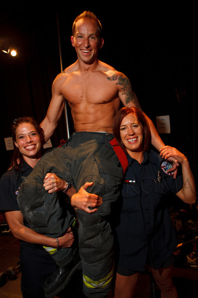 Holding up Chris Zienkievicz are Jennifer Rosely (left) and Jenny Klingmueller.  The 2013 Colorado Firefighter Calendar Auditions & Celebrity Judging Event at Exdo Event Center in Denver, Colorado, on Friday, May 11, 2012.<br /> Photo Steve Peterson